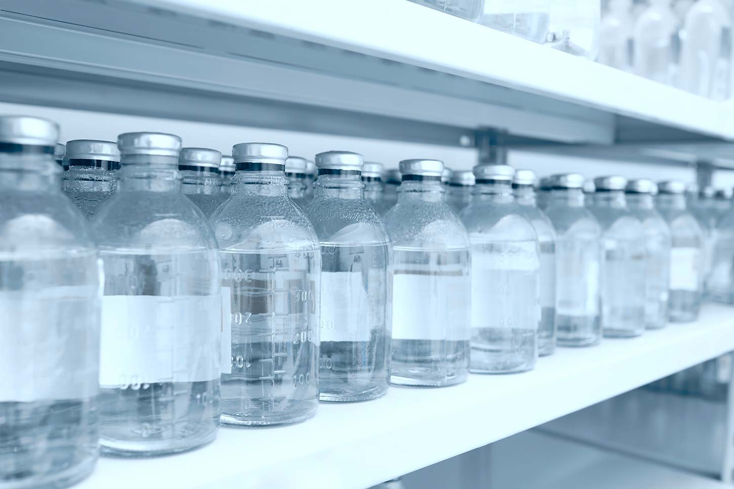 Containers with a clear liquid on white metal shelves