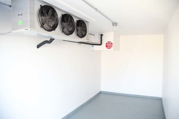 Inside of a Polar King small refrigerated trailer with white walls and three black fans