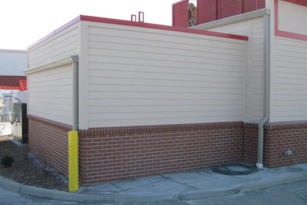 Commercial cooler unit with white side panels, red trim, and brick at the bottom