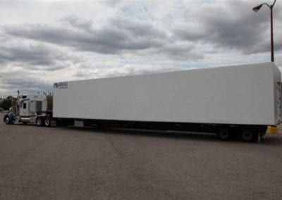 A large truck moving a polar leasing white freezer box rental