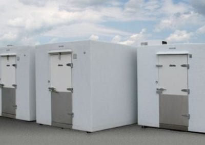 Three large white emergency refrigeration walk-in coolers and freezers outside