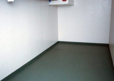 Inside of a polar leasing commercial refrigerator with white walls and grey flooring