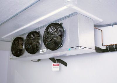Inside of a Polar King industrial freezer with three black fans and white walls