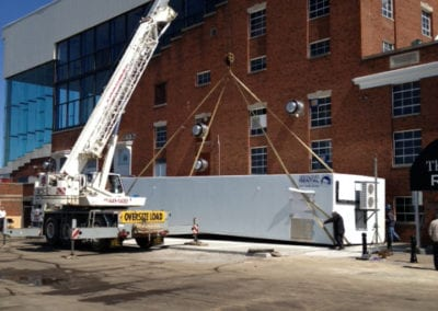 A white crane reaching the top of a brick building with a commercial freezer unit below