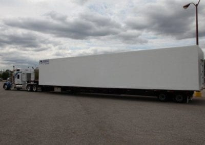 Large white portable walk in cooler on a semi truck